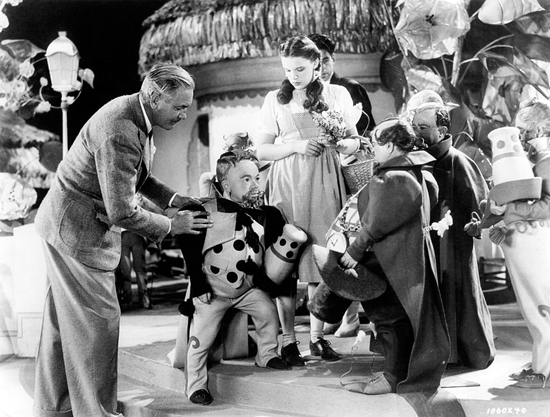 Victor Fleming on the set of The Wizard of Oz directing a Munchkinland sequence with Judy Garland