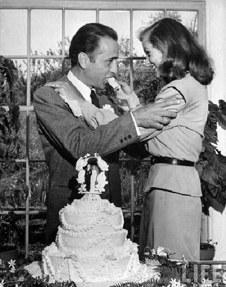 bacall and bogart at their wedding, with cake