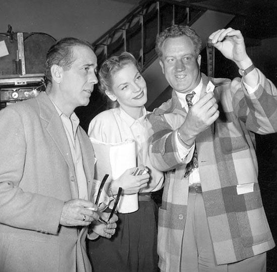 Humphrey Bogart, Lauren Bacall and Delmer Daves looking at negatives of Dark Passage