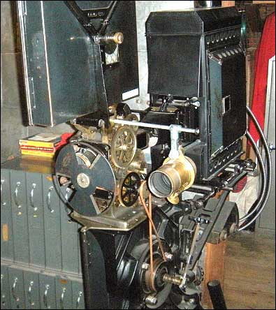 The first silent film projectors were hand-cranked in much the same way cameras of the era were operated. This is an example of such a projector. The large black box at the rear of the projector contained a carbon arc lamp, the projector's light source. The gold-colored lens to the right of the complex-looking film mechanism was used for projecting lantern slides. Lantern slides were used during intermissions to project announcements, local advertising, and the lyrics to songs for audience sing-alongs, a popular movie theater amusement of the day. Photo: HPO collection.