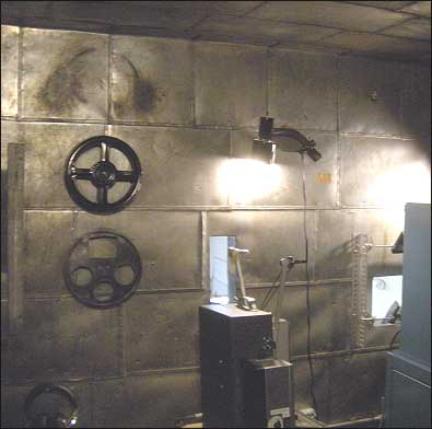 Slightly more modern projectors driven by electric motors have replaced the old hand-crank models originally used in the Edison Niles Theater. Note the tin shielding in this view of the projection booth's front wall. Motion picture film of the era consisted of an emulsion coating on a base of clear nitrate. Since nitrate is extremely flammable there was always a danger of the film catching fire. This was such a common occurrence that all interior surfaces of the projection booth were shielded with metal to protect the audience in the event of a film fire. In later years asbestos replaced metal shielding in most theaters. (NOTE: The silent films shown today in the museum theater are celluloid safety film duplicates of the originals.) Photo: HPO collection.