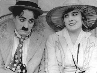 "Chaplin and Purviance in a production still from ""The Cure"" (1917). Photo believed to be in the public domain."