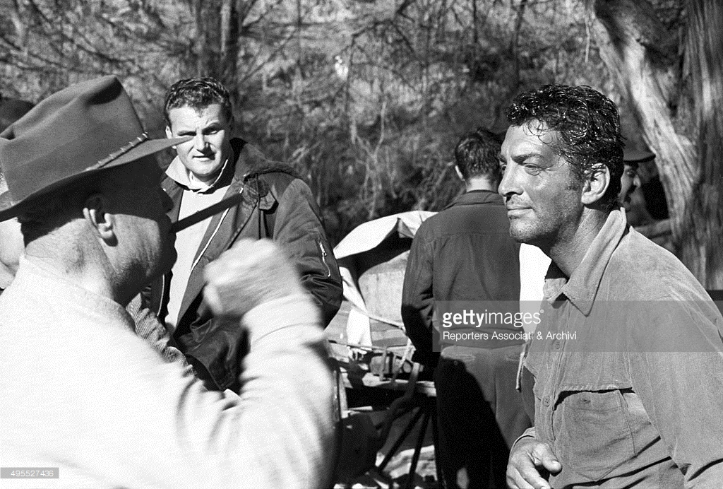 Dean Martin talking to director Henry Hathaway during a break on the set of the film 'The Sons of Katie Elder'