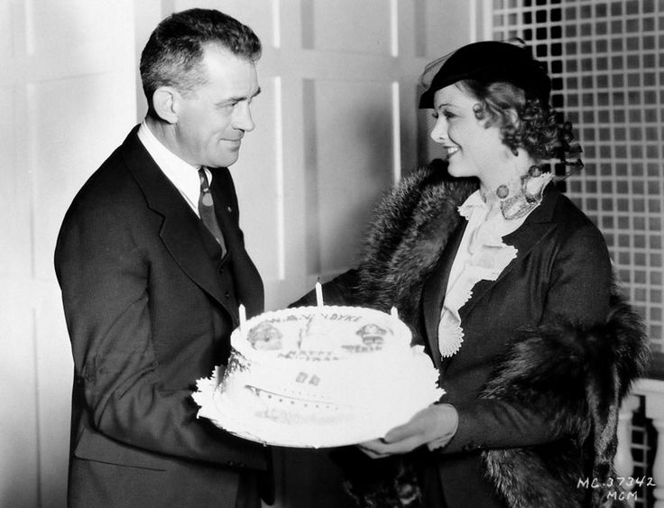 Myrna Loy presents Manhattan Melodrama director W.S. Van Dyke with a birthday cake Myrna Loy