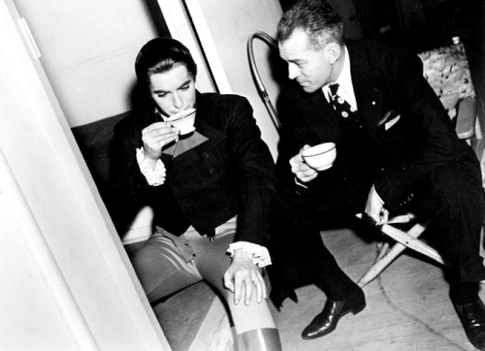 W.S. Van Dyke and Tyrone Power discuss film Marie Antoinette over a hot cup of tea (1938)