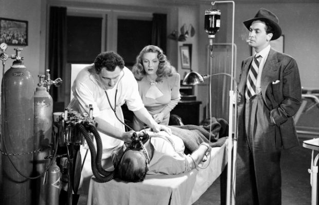 Left to Right: Dr. Craig (Herbert Rudley), Margot Shelby (Jean Gillie), and Jim Vincent (Edward Norris) attempt to bring their boss (Robert Armstrong) back from the dead.