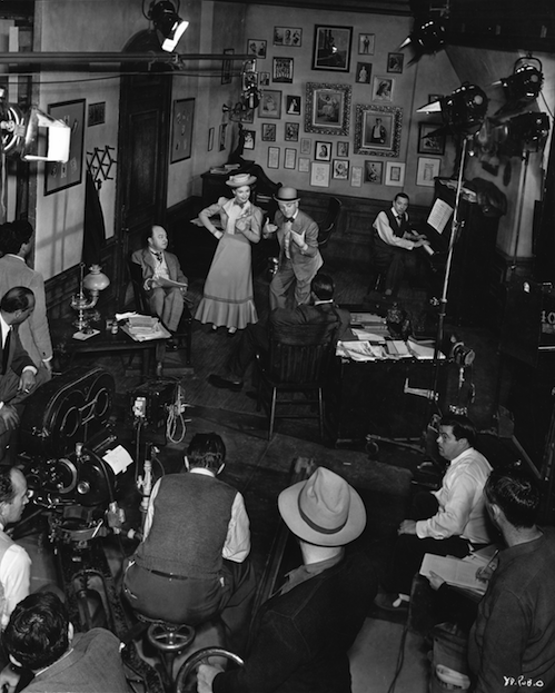 "Curtiz (at far left with cigarette) directs the ""Harrigan"" number with Cagney & Joan Leslie with Chester Clute and George Tobias (back to camera)"