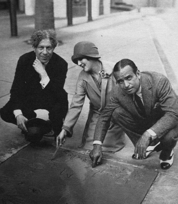 Mary Pickford and Douglas Fairbanks put their hand and footprints in cement at Grauman's Chinese Theater. 1927