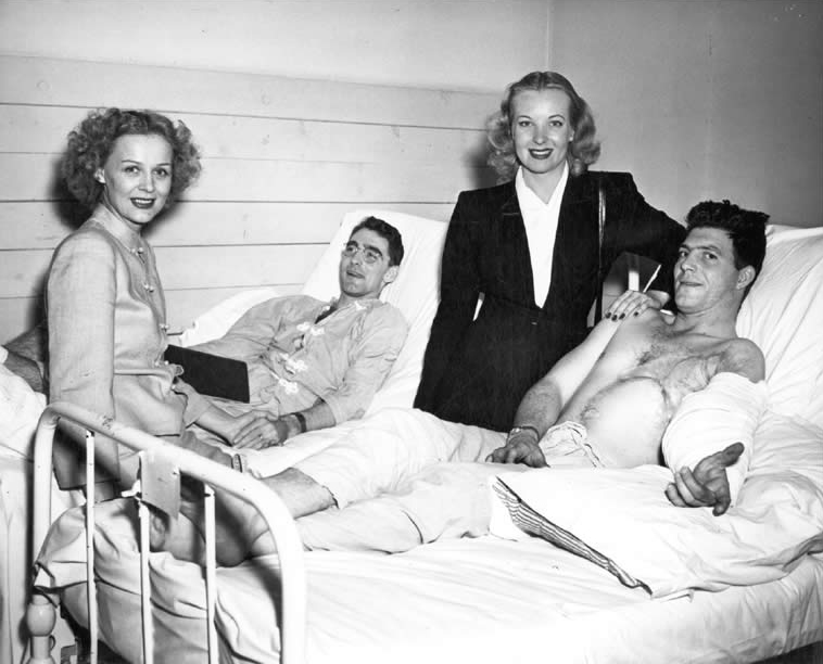 Gloria Stuart and actress Hillary Brooke visiting two convalescing troops at O'Reilly General Hospital in Springfield, Missouri, c. 1944.