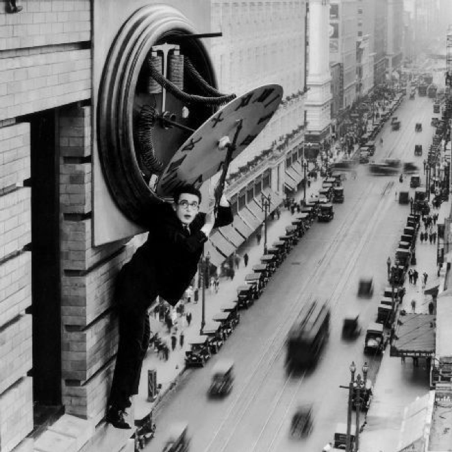 Harold Lloyd hangs from a clock in Safety Last! (1923)