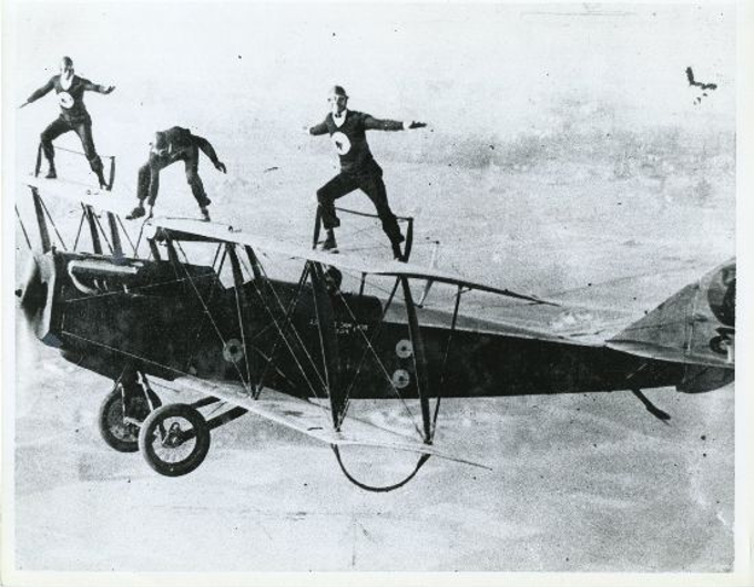 1920s Barnstormers standing on the wings of a plane