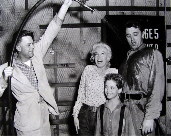 marilyn monroe, tommy rettig, robert mitchum being doused with water on set of river of no return