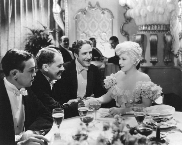 Mae West surrounded by men in Belle of the Nineties